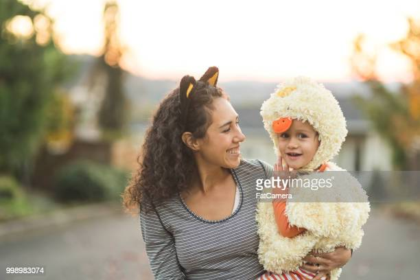 ethnic mom trick or treating with her young son - halloween kids stock photos and pictures