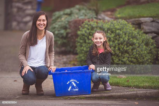 Ethnic mother and daughter sitting by recycling receptacle