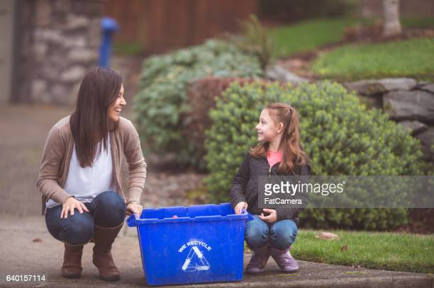Ethnic mother and daughter sitting next to a recyling bin