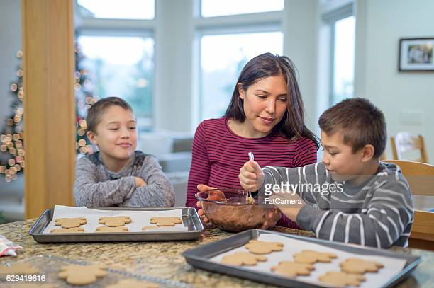 Ethnic mother and sons frosting gingerbread men for Christmas tradition