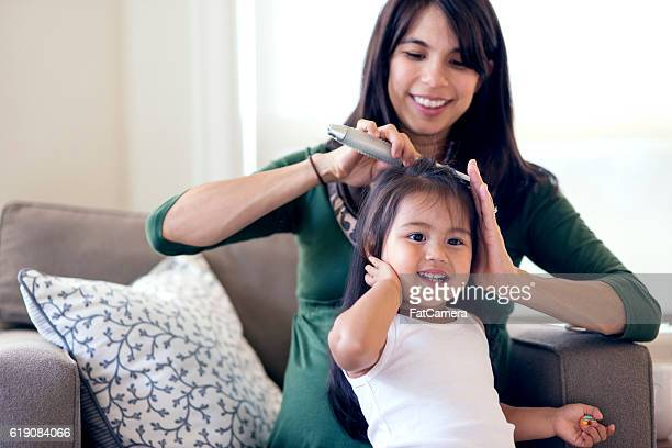 Ethnic mother brushing her young daughters hair