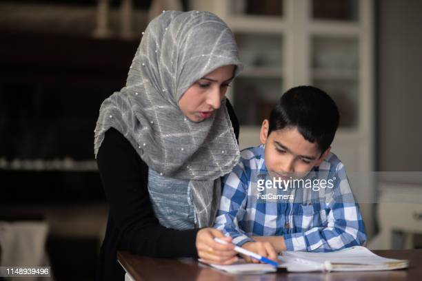 ethnic mother helping her son with homework - islam stock pictures, royalty-free photos & images