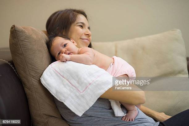Ethnic mother holding newborn baby on a comfy chair