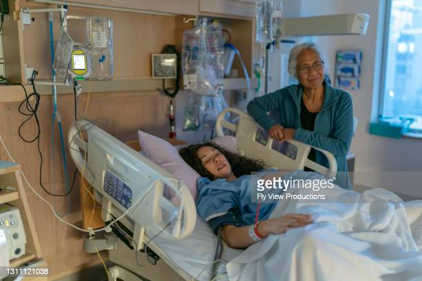 ethnic mother in hospital bed waiting to give birth with mother at her side - ward stock pictures, royalty-free photos & images