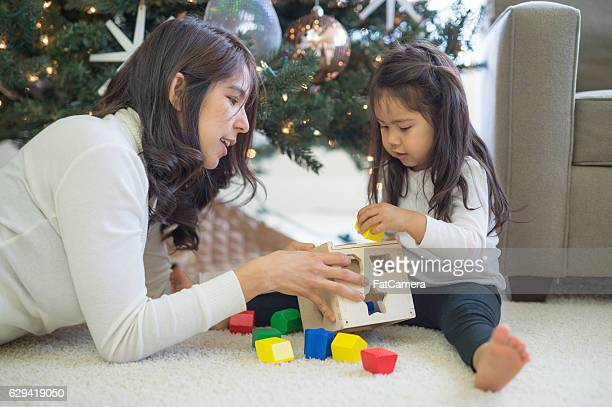 Ethnic mother playing blocks with daughter under christmas tree