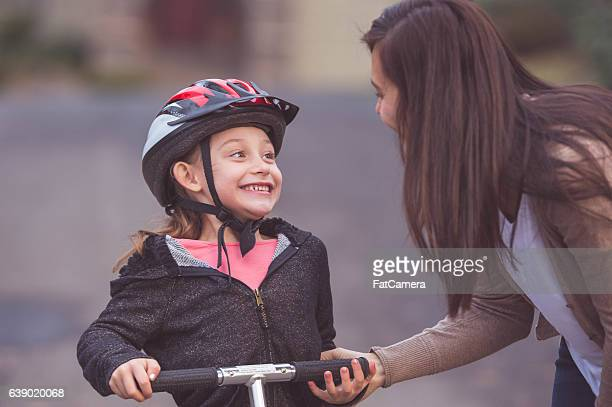 Ethnic mother putting a helmet on her daughter for