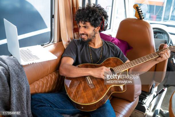 ethnic nomad young man guitar player in motorhome - nomadic people stock pictures, royalty-free photos & images