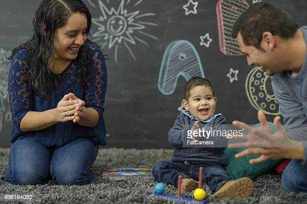 ethnic parents reading with their toddler in a home playroom - mexican ethnicity stock pictures, royalty-free photos & images