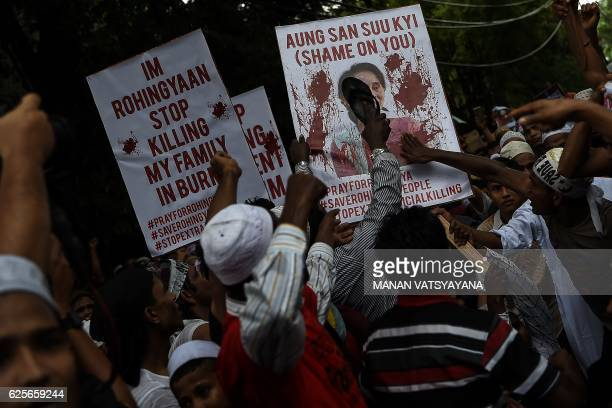 TOPSHOT Ethnic Rohingya Muslim refugees use a shoe to hit a placard with portrait of Myanmar State Counsellor and Foreign Minister Aung San Suu Kyi...