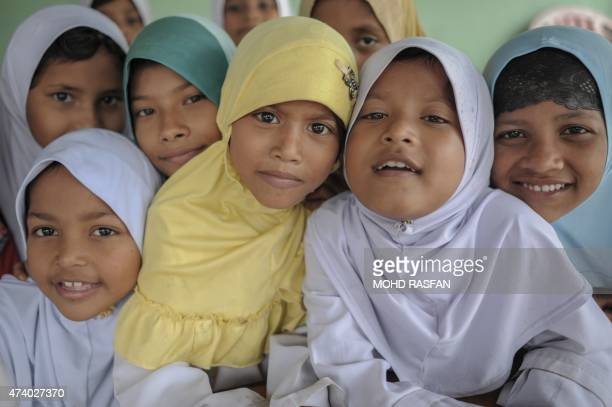 Ethnic Rohingya refugee children from Myanmar residing in Malaysia pose for pictures after having their lunch at their community school in Ampang in...