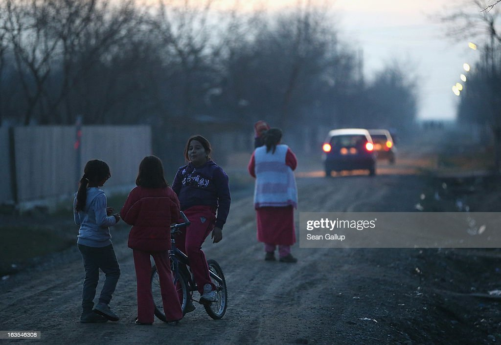 Ethnic Roma children chat on one of the residential streets after sundown on March 11, 2013 in Dilga, Romania. Dilga is a settlement of 2,500 people with dirt roads and no running water, and unemployment is at 70%. Most of the working-age men and women have at some point worked abroad, mostly in Italy or Great Britain, as many say they are unable to find adequate work in Romania. Romania's Roma belong to a myriad of different tribes defined by their craft, and Dilga's belong to a group called the Rudari, who until the 1930s specialised in woodcrafts. During the communist years most worked in nearby state-run factories and agricultural cooperatives, though the majority of these went bankrupt after 1989 and the local Roma lost their jobs. Since then they have struggled to make ends meet and find a better future for their children, though projects initiated by the European Union and NGOs are helping some to launch small-scale enterprises and improve their children's education.