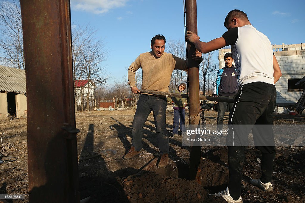 Ethnic Roma Ciprean Costea (C) and his relative Costin Costea, 19, dig out iron columns that were part of a shed to make way for a vegetable garden on the property of Costin's father on March 11, 2013 in Dilga, Romania. Ciprian worked for two years as a construction worker in Italy until he lost his job as the Italian economy suffered. He now works constructiion jobs in Romania and survives on EUR 200 a month. Dilga is a settlement of 2,500 people with dirt roads and no running water, and unemployment is at 70%. Most of the working-age men and women have at some point worked abroad, mostly in Italy or Great Britain, as many say they are unable to find adequate work in Romania. Romania's Roma belong to a myriad of different tribes defined by their craft, and Dilga's belong to a group called the Rudari, who until the 1930s specialised in woodcrafts. During the communist years most worked in nearby state-run factories and agricultural cooperatives, though the majority of these went bankrupt after 1989 and the local Roma lost their jobs. Since then they have struggled to make ends meet and find a better future for their children, though projects initiated by the European Union and NGOs are helping some to launch small-scale enterprises and improve their children's education.