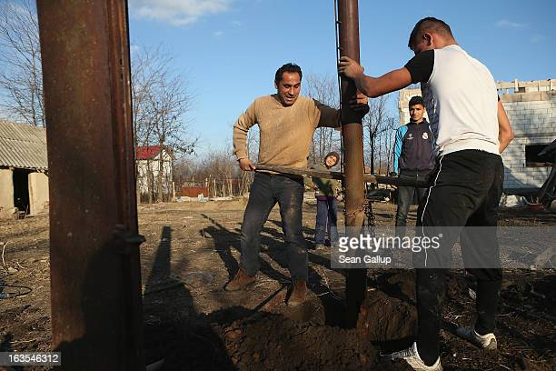 Ethnic Roma Ciprean Costea and his relative Costin Costea dig out iron columns that were part of a shed to make way for a vegetable garden on the...