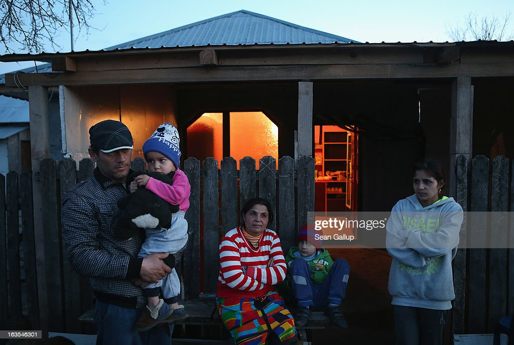 Ethnic Roma Xenia Costea (R), her father (L) and other members of her family stand outside the small grocery shop she runs on March 11, 2013 in Dilga, Romania. Xenia says hers is one of six small shops in Dilga and that many of her customers buy on credit. Dilga is a settlement of 2,500 people with dirt roads and no running water, and unemployment is at 70%. Most of the working-age men and women have at some point worked abroad, mostly in Italy or Great Britain, as many say they are unable to find adequate work in Romania. Romania's Roma belong to a myriad of different tribes defined by their craft, and Dilga's belong to a group called the Rudari, who until the 1930s specialised in woodcrafts. During the communist years most worked in nearby state-run factories and agricultural cooperatives, though the majority of these went bankrupt after 1989 and the local Roma lost their jobs. Since then they have struggled to make ends meet and find a better future for their children, though projects initiated by the European Union and NGOs are helping some to launch small-scale enterprises and improve their children's education.