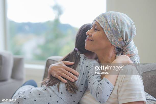 Ethnic senior adult female with cancer hugging her grandchild