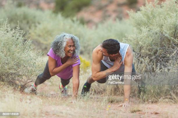 Ethnic senior woman exercising with her personal trainer