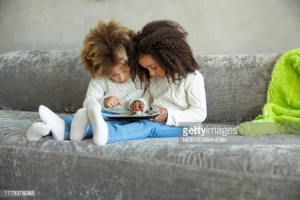 filles ethniques de gosses de soeur jouant avec le pc de tablette - seulement des enfants photos et images de collection
