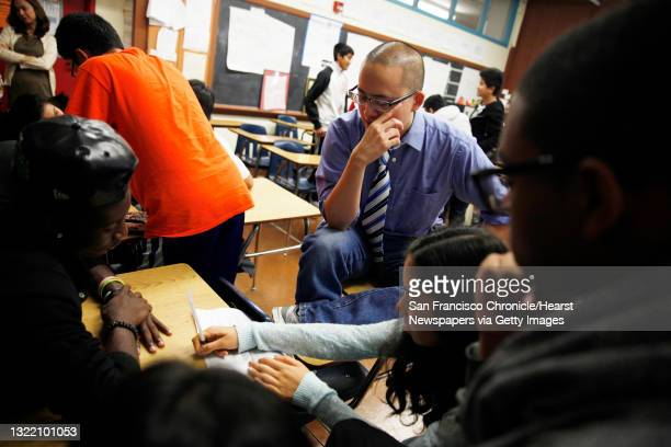 Ethnic studies teacher David Ko works with students as they work on a classroom exercise brainstorming a topic and research questions at Washington...