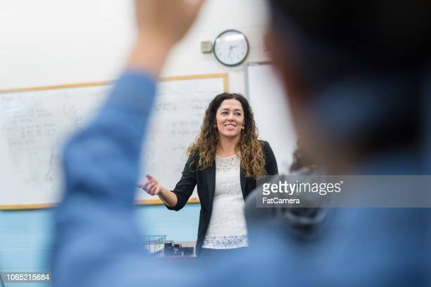 ethnic teacher points to one of her students with a raised hand - high school stock pictures, royalty-free photos & images