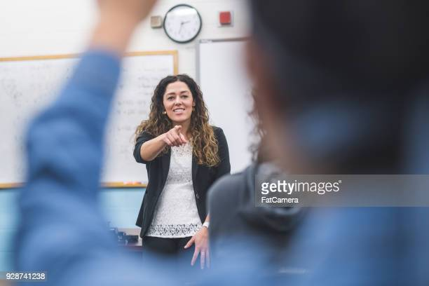 ethnic teacher points to one of her students with a raised hand - teacher stock pictures, royalty-free photos & images