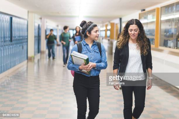 ethnic teacher walks with one of her students down the hallway - small group of people stock pictures, royalty-free photos & images