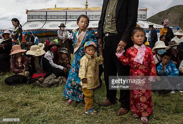 Ethnic Tibetan nomad children wear fancy dress as they watch a horse festival on July 26 2015 on the Tibetan Plateau in Yushu County Qinghai China...