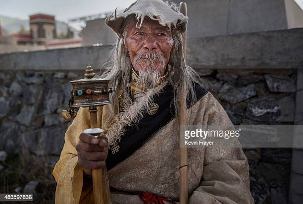 A ethnic Tibetan nomad uses a prayer wheel as he watches on July 24 2015 at a local government sponsored festival on the Tibetan Plateau in Yushu...