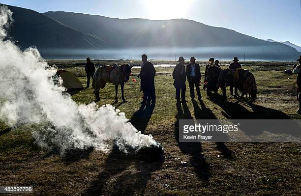Ethnic Tibetan nomads burn juniper as a ritual to cleanse their horses for good luck before racing at a local government sponsored festival on July...