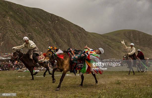 Ethnic Tibetan nomads perform skills during a riding competition at a local government sponsored festival on July 26 2015 on the Tibetan Plateau in...