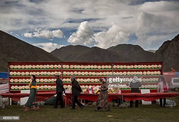 Ethnic Tibetan nomads walks passed a carnival game on July 25 2015 at a local government sponsored festival on the Tibetan Plateau in Yushu County...