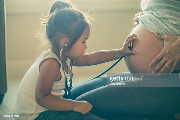 ethnic toddler listening to her mothers pregnant tummy - fat belly girl stock photos and pictures