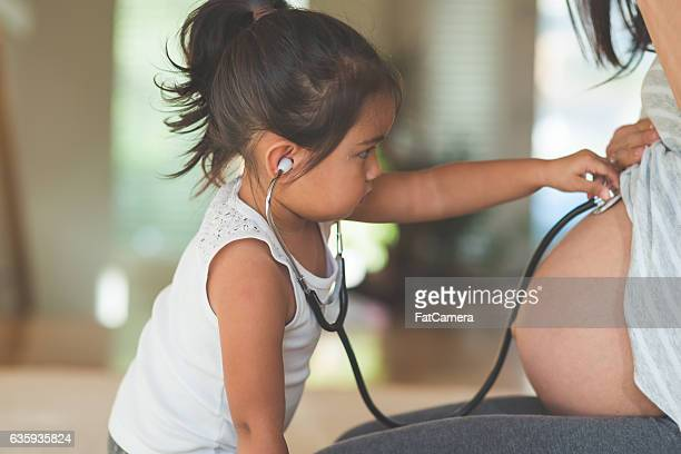 Ethnic toddler listening to her mothers pregnant tummy