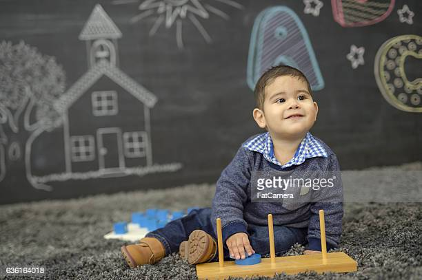 Ethnic toddler playing with his toys in a daycare