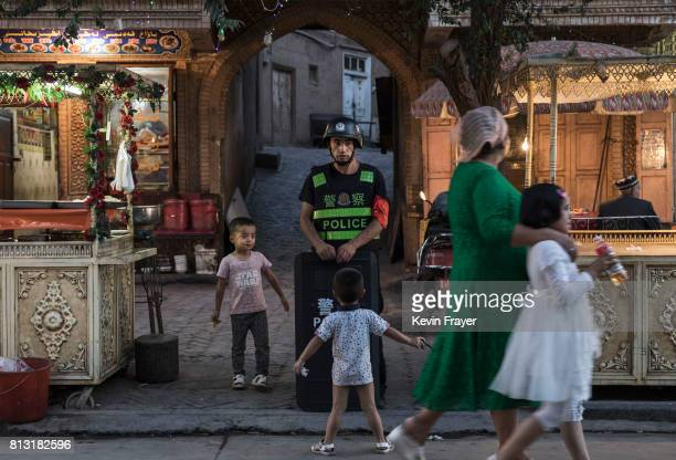 Ethnic Uyghur children joke as they taunt a local police officer on June 29 2017 in the old town of Kashgar in the far western Xinjiang province...