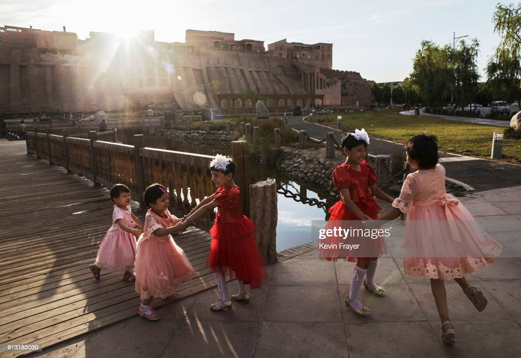 Ethnic Uyghur girls dance on the holiday of Eid Al Fitr on June 26, 2017 in the old town of Kashgar, in the far western Xinjiang province, China. Kashgar has long been considered the cultural heart of Xinjiang for the province's nearly 10 million Muslim Uyghurs. At an historic crossroads linking China to Asia, the Middle East, and Europe, the city has changed under Chinese rule with government development, unofficial Han Chinese settlement to the western province, and restrictions imposed by the Communist Party. Beijing says it regards Kashgar's development as an improvement to the local economy, but many Uyghurs consider it a threat that is eroding their language, traditions, and cultural identity. The friction has fuelled a separatist movement that has sometimes turned violent, triggering a crackdown on what China's government considers 'terrorist acts' by religious extremists. Tension has increased with stepped up security in the city and the enforcement of measures including restrictions at mosques.
