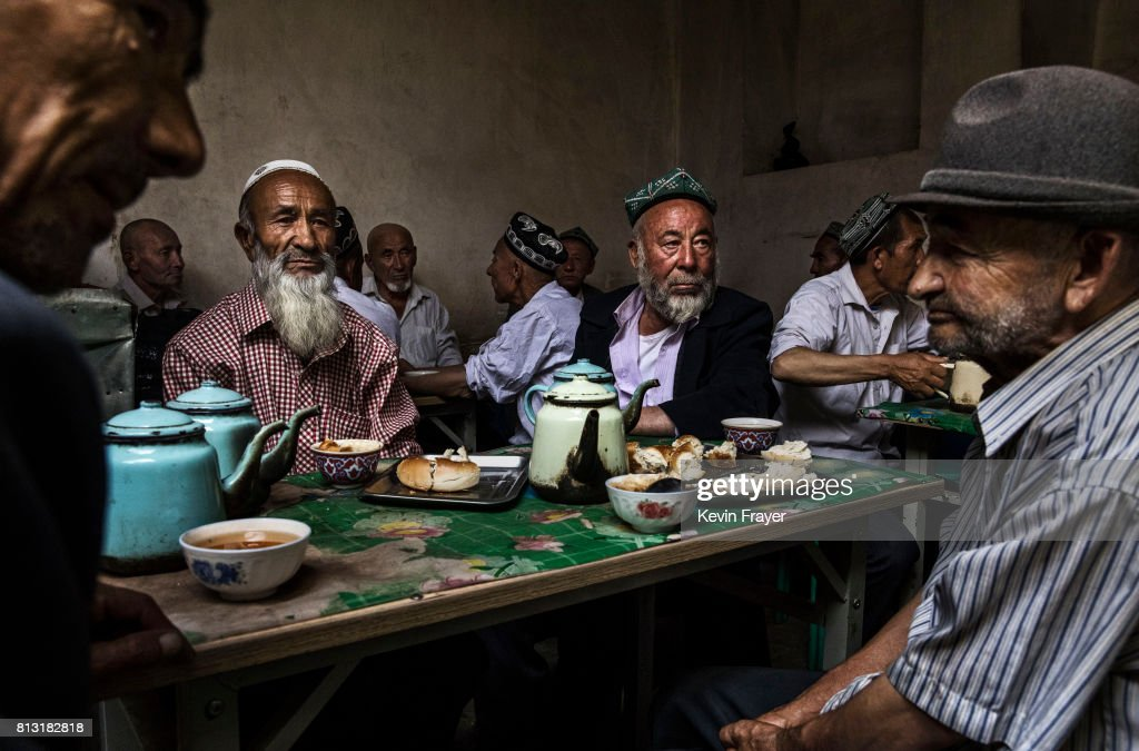 Ethnic Uyghur men talk as they meet at a teahouse on July 1, 2017 in the old town of Kashgar, in the far western Xinjiang province, China. Kashgar has long been considered the cultural heart of Xinjiang for the province's nearly 10 million Muslim Uyghurs. At an historic crossroads linking China to Asia, the Middle East, and Europe, the city has changed under Chinese rule with government development, unofficial Han Chinese settlement to the western province, and restrictions imposed by the Communist Party. Beijing says it regards Kashgar's development as an improvement to the local economy, but many Uyghurs consider it a threat that is eroding their language, traditions, and cultural identity. The friction has fuelled a separatist movement that has sometimes turned violent, triggering a crackdown on what China's government considers 'terrorist acts' by religious extremists. Tension has increased with stepped up security in the city and the enforcement of measures including restrictions at mosques.