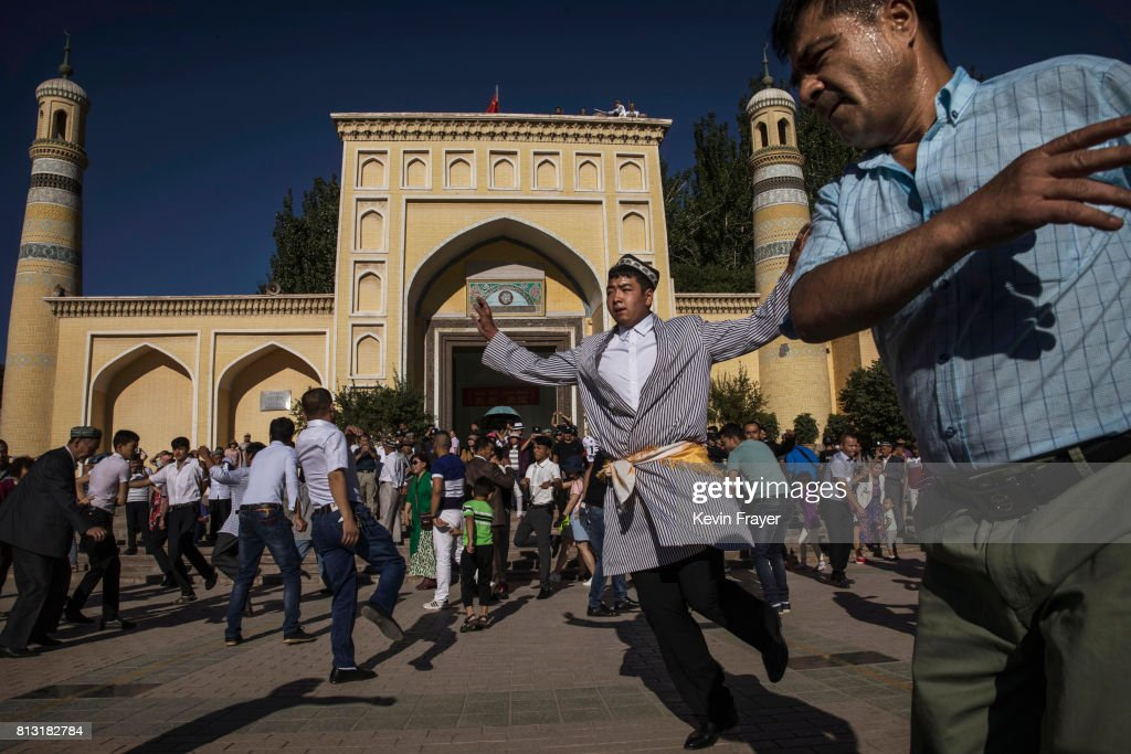 Ethnic Uyghur men who were organized by local party officials, dance after prayers marking Eid Al Fitr outside Id Kah Mosque on June 26, 2017 in the old town of Kashgar, in the far western Xinjiang province, China. Kashgar has long been considered the cultural heart of Xinjiang for the province's nearly 10 million Muslim Uyghurs. At an historic crossroads linking China to Asia, the Middle East, and Europe, the city has changed under Chinese rule with government development, unofficial Han Chinese settlement to the western province, and restrictions imposed by the Communist Party. Beijing says it regards Kashgar's development as an improvement to the local economy, but many Uyghurs consider it a threat that is eroding their language, traditions, and cultural identity. The friction has fuelled a separatist movement that has sometimes turned violent, triggering a crackdown on what China's government considers 'terrorist acts' by religious extremists. Tension has increased with stepped up security in the city and the enforcement of measures including restrictions at mosques.