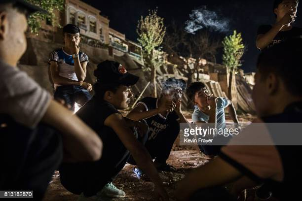 Ethnic Uyghur teenagers chat as they sit together on July 1 2017 in the old town of Kashgar in the far western Xinjiang province China Kashgar has...