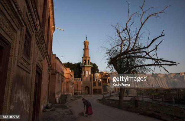 A ethnic Uyghur woman sweeps outside her house on July 1 2017 in the old town of Kashgar in the far western Xinjiang province China Kashgar has long...