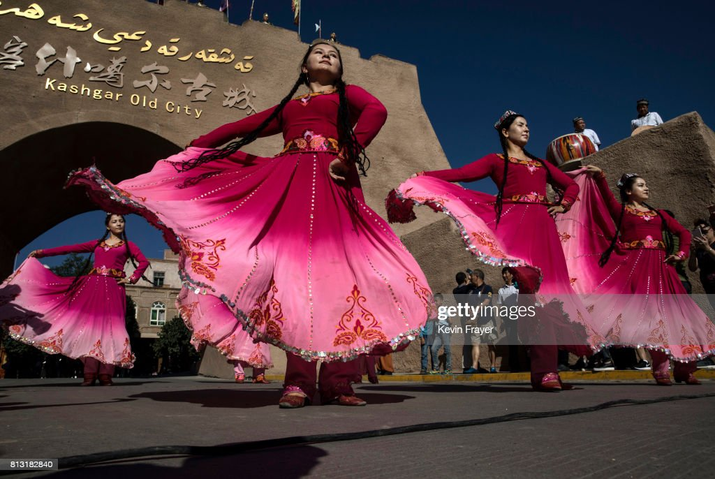 Ethnic Uyghur women dance for Chinese tourists on June 29, 2017 in the old town of Kashgar, in the far western Xinjiang province, China. Kashgar has long been considered the cultural heart of Xinjiang for the province's nearly 10 million Muslim Uyghurs. At an historic crossroads linking China to Asia, the Middle East, and Europe, the city has changed under Chinese rule with government development, unofficial Han Chinese settlement to the western province, and restrictions imposed by the Communist Party. Beijing says it regards Kashgar's development as an improvement to the local economy, but many Uyghurs consider it a threat that is eroding their language, traditions, and cultural identity. The friction has fuelled a separatist movement that has sometimes turned violent, triggering a crackdown on what China's government considers 'terrorist acts' by religious extremists. Tension has increased with stepped up security in the city and the enforcement of measures including restrictions at mosques.
