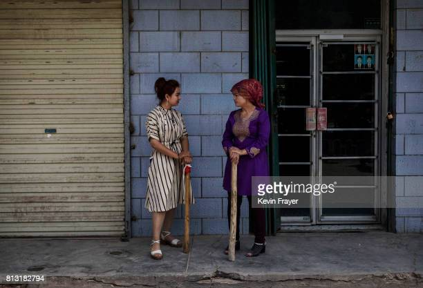 Ethnic Uyghur women that have been trained by local police hold wooden clubs as they guard a street on June 28 2017 in the old town of Kashgar in the...