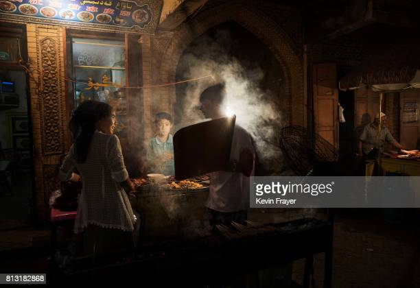 Ethnic Uyghurs cook food at their restaurant in a local market on June 25 2017 in the old town of Kashgar in the far western Xinjiang province China...