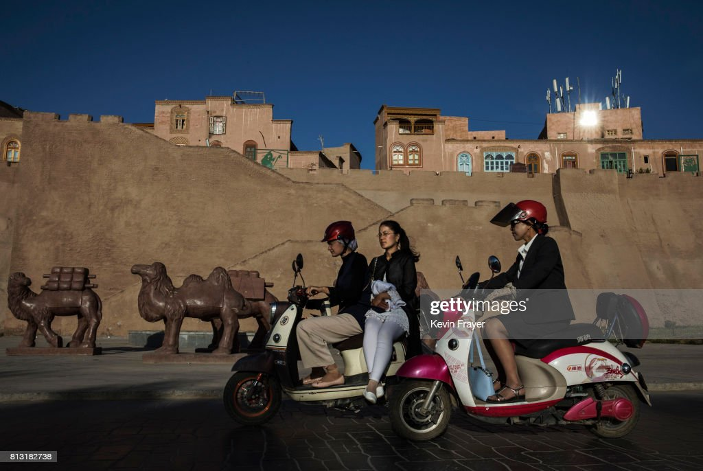 Ethnic Uyghurs ride by a newly finished section of the old city walls on June 30, 2017 in the old town of Kashgar, in the far western Xinjiang province, China. Kashgar has long been considered the cultural heart of Xinjiang for the province's nearly 10 million Muslim Uyghurs. At an historic crossroads linking China to Asia, the Middle East, and Europe, the city has changed under Chinese rule with government development, unofficial Han Chinese settlement to the western province, and restrictions imposed by the Communist Party. Beijing says it regards Kashgar's development as an improvement to the local economy, but many Uyghurs consider it a threat that is eroding their language, traditions, and cultural identity. The friction has fuelled a separatist movement that has sometimes turned violent, triggering a crackdown on what China's government considers 'terrorist acts' by religious extremists. Tension has increased with stepped up security in the city and the enforcement of measures including restrictions at mosques.