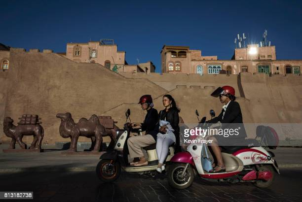 Ethnic Uyghurs ride by a newly finished section of the old city walls on June 30 2017 in the old town of Kashgar in the far western Xinjiang province...