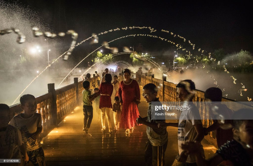 Ethnic Uyghurs take in a new laser and water show as part of local government tourism development on June 30, 2017 in the old town of Kashgar, in the far western Xinjiang province, China. Kashgar has long been considered the cultural heart of Xinjiang for the province's nearly 10 million Muslim Uyghurs. At an historic crossroads linking China to Asia, the Middle East, and Europe, the city has changed under Chinese rule with government development, unofficial Han Chinese settlement to the western province, and restrictions imposed by the Communist Party. Beijing says it regards Kashgar's development as an improvement to the local economy, but many Uyghurs consider it a threat that is eroding their language, traditions, and cultural identity. The friction has fuelled a separatist movement that has sometimes turned violent, triggering a crackdown on what China's government considers 'terrorist acts' by religious extremists. Tension has increased with stepped up security in the city and the enforcement of measures including restrictions at mosques.