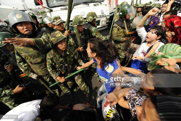 Ethnic Uygur women protest towards Chinese riot police as they demonstrate in Urumqi in China's far west Xinjiang province on July 7, 2009. Police...