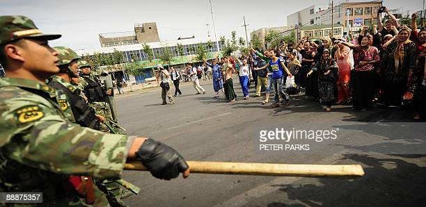 Ethnic Uygur women protest towards Chinese riot police in Urumqi in China's far west Xinjiang province on July 7 2009 Police fired clouds of acrid...