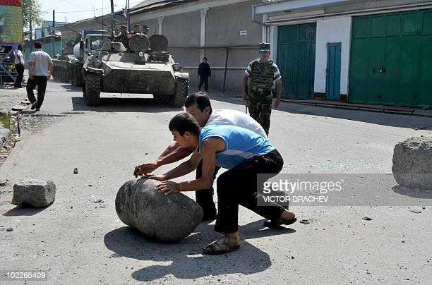 Ethnic Uzbeks and Kyrgyz jointly dismantle a street barricade on the border of Uzbek district in the southern city of Osh on June 20, 2010....