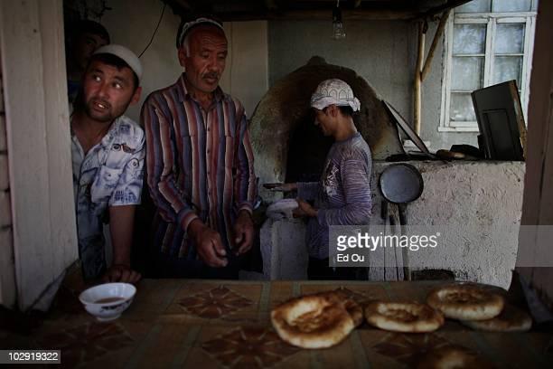 Ethnic Uzbeks use a oven to make 'tandir nan' a traditional bread in an Uzbek enclave in Osh Kyrgyzstan June 16 2010 Basic supplies such as flour gas...