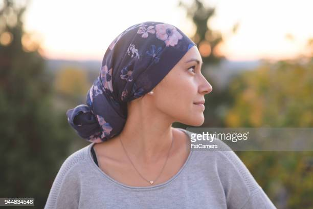 ethnic woman battling cancer stands outside and contemplates her life - cancer stock photos and pictures